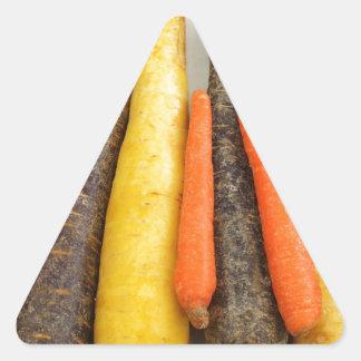 Zanahorias amarillas y anaranjadas púrpuras crudas pegatina triangular