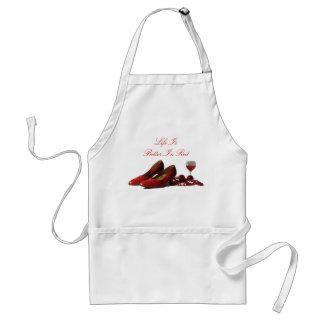 Zapatos rojos del tacón alto y vino rojo delantal