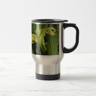 Zucchini plant in blossom in the vegetable garden travel mug